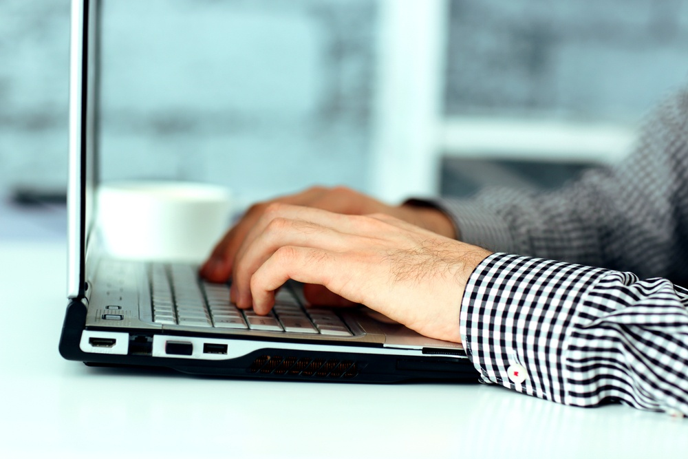 Closeup image of a male hands typing on laptop keyboard.jpeg